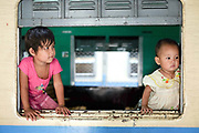 Children look out of a carriage window of a train at Mandalay station on 25th May 2016 in Myanmar