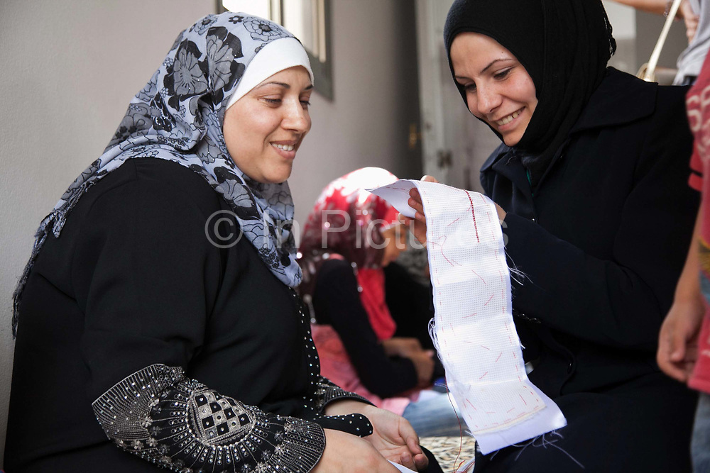 Delal's daughter shows a woman how to stitch. Delal is a Syrian Palestinian refugee from Damascus. She now lives in Shatila camp with her family after they fled the war in Syria. She runs workshops with her adult daughter where they teach other Syrian women refugees traditional handy craft.