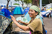 23 NOVEMBER 2012 - BANGKOK, THAILAND:  A Pitak Siam anti-government protester sets up her tent in Bangkok Friday. Thai authorities have imposed the Internal Security Act (ISA), that enables police to call on the army if needed to keep order, and placed thousands of riot police in the streets around Government House in anticipation of a large anti-government protest Saturday. The group sponsoring the protest, Pitak Siam, said up to 500,000 people could turn out to protest against the government. They are protesting against corruption in the current government and the government's unwillingness to arrest or pursue fugitive former Prime Minister Thaksin Shinawatra, deposed in 2006 coup and later convicted on corruption charges. The current Thai Prime Minister is Yingluck Shinawatra, Thaksin's sister.      PHOTO BY JACK KURTZ
