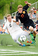 Jackson senior Kevin Krause takes a hit from Worland senior Connor Warner on Saturday as the Broncs take the Warriors for a ride in the 3A Wyoming State Soccer Championship. Jackson shut out Worland and won the title game 4-0.