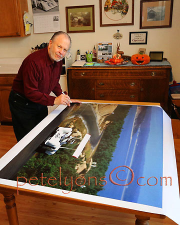 Pete about to autograph Jumbo (58x44-inch) print of his 1968 Chaparral image on dining room table at Big Bear City 12Nov2014; Photo by Lorna Lyons 2014; © 2014 petelyons.com