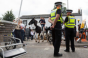 Police watch over the towns main road as two boys on horseback approach two girls at a crossing at Appleby Horse Fair, the biggest gathering of Gypsies and travellers in Europe, on 14th August, 2021 in Appleby, United Kingdom. Appleby Horse Fair attracts thousands from Gypsy, Romany, and traveller communities annually, making it the biggest gathering of its kind in Europe. Generally held for a week every June, the fair was postponed in 2020 and pushed forward to August in 2021 due to Coronavirus.