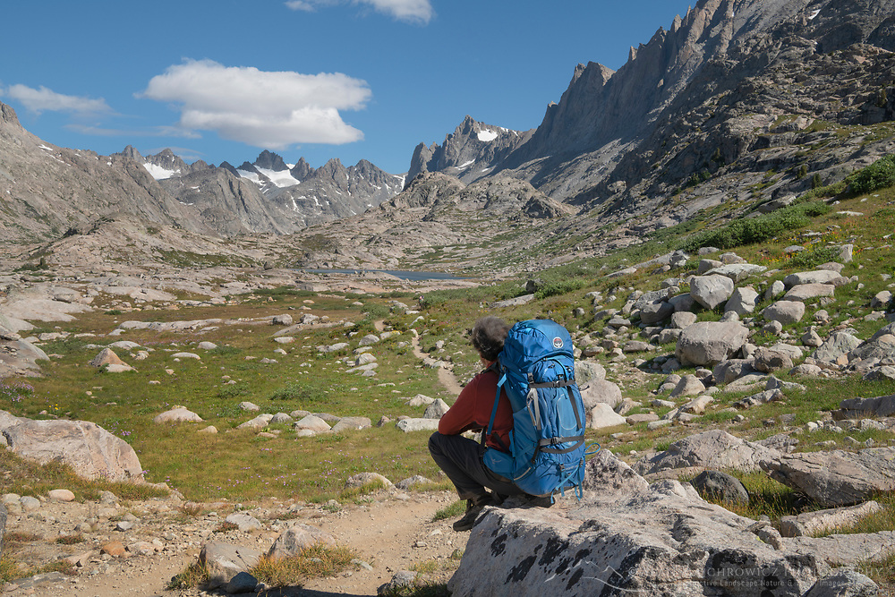 Adult male backpacker with blue backpack and red shirt enjoying the view from the Titcomb Basin Trail, Bridger Wilderness, Wind River Range Wyoming