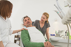 Female dentist and dental assistant talking to patient , Munich, Bavaria, Germany