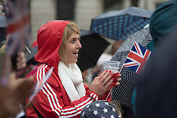 Trafalgar Square, London, June 12th 2016. Rain greets Londoners and visitors to the capital's Trafalgar Square as the Mayor hosts a Patron's Lunch in celebration of The Queen's 90th birthday. PICTURED: A woman applauds the performers on the stage.