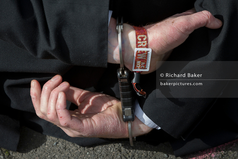 A detail of hands in handcuffs after an environmental activist has been arrested while protesting about Climate Change during the occupation of City Airport (London's Business Travel hub) in east London, the fourth day of a two-week prolonged worldwide protest by members of Extinction Rebellion, on 10th October 2019, in London, England.