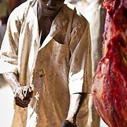 Chopping up meat at the Sunday market. Near Koumbadiouma in Kolda, Senegal.