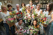 """Rachel running a Sunday morning flower arranging course at 'Green and Gorgeous'. Rachel and course participants show the fruits of their work at the end of their morning course in flower arrangement.<br /><br />Rachel is the owner of """"Green and Gorgeous"""" Flower Farm in Oxfordshire. She is well known for the flower arranging courses she offers. Her flower farm also caters for events, weddings and private picking<br /><br />British local flowers, grown nearby, count for around 10% of the UK market, traveling less than a tenth of their foreign counterparts which are often flown in from abroad. Nearly 90% of the flowers sold in the UK are actually imported, and many travel over 3000 miles. Local flower farms help biodiversity, providing food and habitat to a huge variety of wildlife, insects including butterflies, bugs, and bees. Often local flower farmers prefer to grow organic rather than using pesticides. British flowers bloom all the year around, even in the depths of winter, and there are local flower farms throughout the country.<br /><br />Many people like the idea of the just picked from the garden look, and come to flower farms throughout Britain to pick their own for weddings, parties and garden fetes. Others come for the joy of a day out in the countryside with their family. Often a bride and her family will come to pick the flowers for her own wedding, some even plant the seeds earlier in the year."""