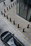 As workers in London largely remain working from home during the Coronavirus pandemic, a single figure walks through an urban street landscape of road markings and traffic bollards and where a courier's vehicle has on its rear the name 'Capital', in the City of London, the capital's financial district, on 4th September 2020, in London, England.