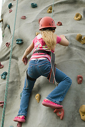 Young girl ascending the climbing wall at a Parklife summer activities event,