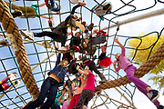 PRICE CHAMBERS / NEWS&GUIDE<br /> Climbing, dangling, balancing or just sitting on a giant rope, students try out the new playground at Wilson Elementary School on Oct. 7. The new equipment offers many more places to spin, slide, swing and climb.