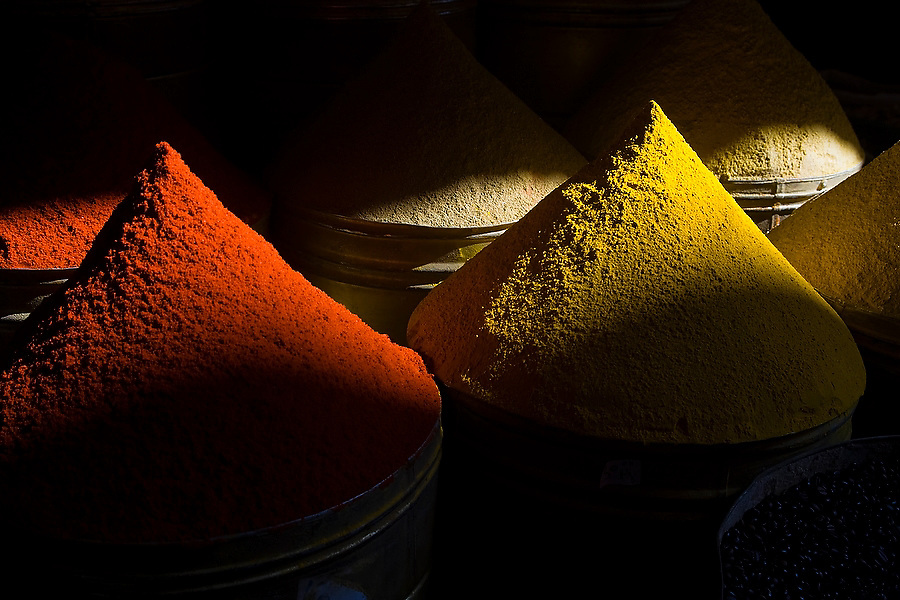 Neat mounds of colorful spices on sale in a storefront in the Marrakech medina, Morocco are lit by a shaft of light on November 15, 2007.