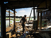 16 OCTOBER 2015 - BANGKOK, THAILAND: Demolition workers tear down houses in the Wat Kalayanamit neighborhood. Fifty-four homes around Wat Kalayanamit, a historic Buddhist temple on the Chao Phraya River in the Thonburi section of Bangkok, are being razed and the residents evicted to make way for new development at the temple. The abbot of the temple said he was evicting the residents, who have lived on the temple grounds for generations, because their homes are unsafe and because he wants to improve the temple grounds. The evictions are a part of a Bangkok trend, especially along the Chao Phraya River and BTS light rail lines. Low income people are being evicted from their long time homes to make way for urban renewal.    PHOTO BY JACK KURTZ