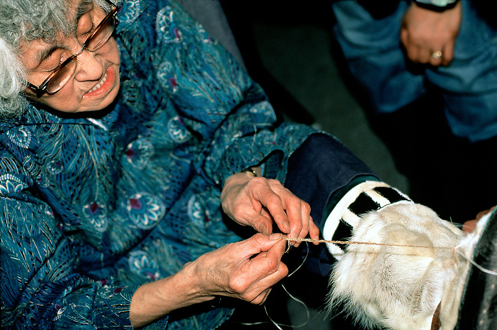 Barrow, Alaska, Elderly woman braiding caribou sinew for use in traditional Alaska Native crafts such as the caribou hide muktuks she is wearing