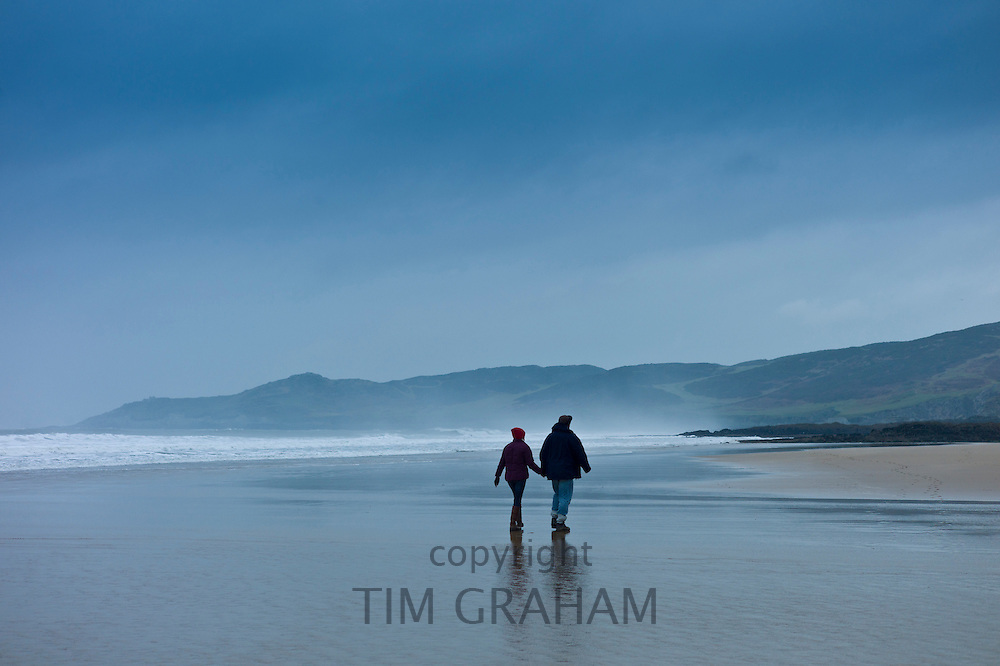 Couple walking along the beach at Woolacombe, North Devon, UK