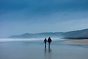 Couple walking along the beach at Woolacombe, North Devon, UK