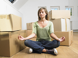May 01, 2007 - Woman doing yoga with moving boxes around her.. Model and Property Released (MR&PR) (Credit Image: © Cultura/ZUMAPRESS.com)