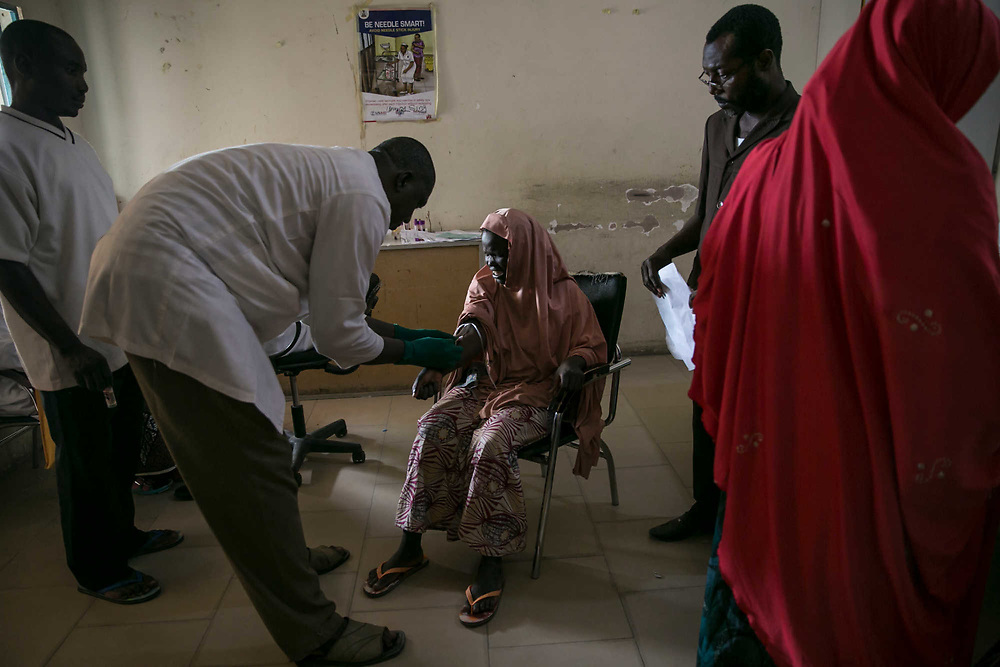 """Amina, 15, center, reacts after a doctor injects a syringe for blood test for syphilis and HIV at a hospital in Maiduguri, Nigeria, April 23, 2019. Amina, who was blind and forcibly married to another blind man inside a Boko Haram camp in 2015, was raped by an IDP man after she escaped and settled in an IDP camp in the outskirts of Maiduguri four days before this photo was taken. The man was arrested, but he was soon to be released by a bail. Amina said, """"I just want justice."""" The results of the blood test for both diseases were negative."""