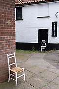 A landscape of anachronism with modern-era chairs and a sign for a nearby antiques business in a rural English town, on 30th June 2021, in Aylsham, Norfolk, England.