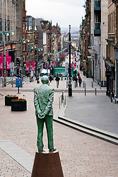 Glasgow, Scotland, UK. 1 April, 2020. Effects of Coronavirus lockdown on Glasgow life, Scotland.  Public walk past statue of Donald Dewar on a quiet Buchanan Street.