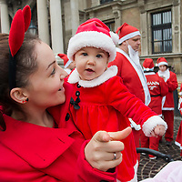 Child in Santa Claus costume and her mother attend the first ever mass Santa Run in central Budapest, Hungary on December 06, 2014. ATTILA VOLGYI