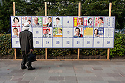 An older man looks at an election board with posters for each of the political candidates for the Upper House election on it. Tokyo, Japan. Tuesday July 16th 2013
