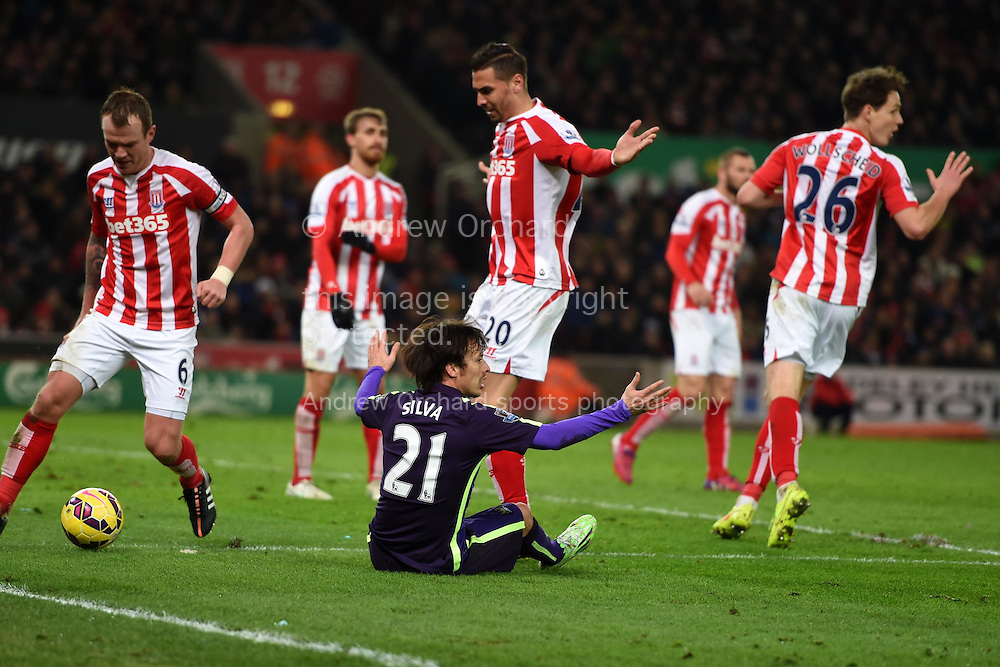 Geoff Cameron of Stoke city (20) fouls David Silva of Manchester city and a penalty is awarded. Barclays Premier League match, Stoke city v Manchester city at the Britannia Stadium in Stoke on Trent , Staffs on Wed 11th Feb 2015.<br /> pic by Andrew Orchard, Andrew Orchard sports photography.