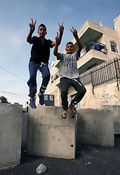 19.10.2015, Jerusalem, ISR, Gewalt zwischen Palästinensern und Israelis, im Bild Kontrollen der Israelischen Sicherheitskräfte im Palästinenser Gebiet // Palestinian boys jump over cement blocks at a newly erected checkpoint in Jerusalem's neighborhood of Jabal al-Mokaber on October 19, 2015. Israeli police began erecting a wall in east Jerusalem to protect a Jewish neighbourhood subject to firebomb and stone attacks launched from an adjacent Palestinian village, Israel on 2015/10/19. EXPA Pictures © 2015, PhotoCredit: EXPA/ APAimages/ Mahfouz Abu Turk<br /> <br /> *****ATTENTION - for AUT, GER, SUI, ITA, POL, CRO, SRB only*****