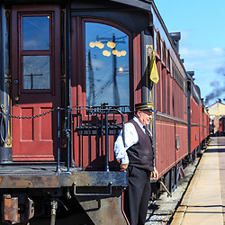 Strasburg, PA, USA - October 6, 2015: A conductor on the Strasburg Rail Road steam locomotive as it leaves at the train station.