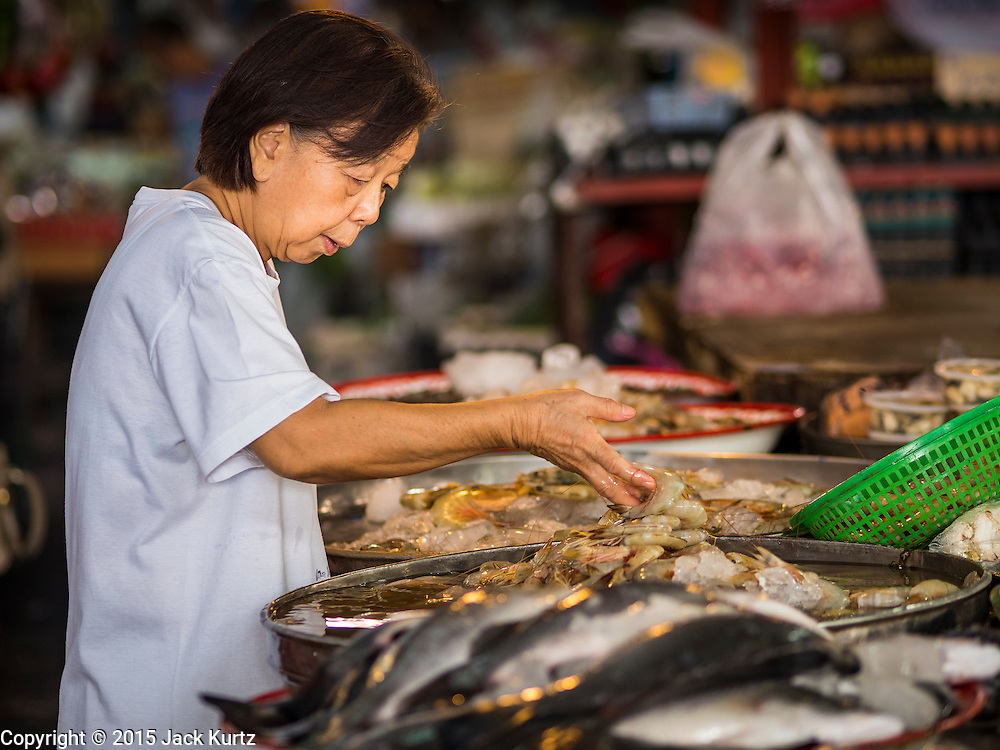 02 SEPTEMBER 2015 - BANGKOK, THAILAND: A customer buys shrimp in Bang Chak Market. The Bang Chak Market serves the community around Sois 91-97 on Sukhumvit Road in the Bangkok suburbs. About half of the market has been torn down, vendors in the remaining part of the market said they expect to be evicted by the end of the year. The old market, and many of the small working class shophouses and apartments near the market are being being torn down. People who live in the area said condominiums are being built on the land.         PHOTO BY JACK KURTZ