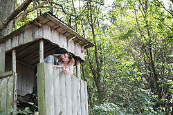 Young couple kissing on lookout tower in a forest, Bavaria, Germany