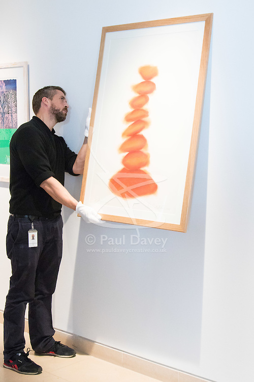 """Christies, St James, London, March 4th 2016. A gallery technician hangs David Nash's """"Column"""", pastel on paper, created especially for the auction at the preview for the It's Our World charity auction at Christie's. Over 40 leading artists including David Hockney, Sir Antony Gormley, David Nash, Sir Peter Blake, Yinka Shonibare, Sir Quentin Blake, Emily Young and Maggi Hambling have committed artworks to the It's Our World Auction in support of The Big Draw and Jupiter Artland Foundation, to be sold at Christie's London on 10 March 2016."""