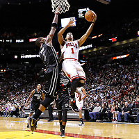 29 January 2012: Chicago Bulls point guard Derrick Rose (1) goes for the lay up past Miami Heat power forward Chris Bosh (1) during the Miami Heat 97-93 victory over the Chicago Bulls at the AmericanAirlines Arena, Miami, Florida, USA.