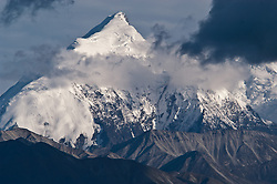 Mount Brooks, a 11,940 foot tall peak, towers over smaller mountains in the Alaska Range as seen from the Wonder Lake campground in Denali National Park and Preserve in Alaska.