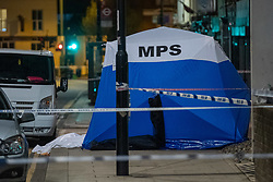 © Licensed to London News Pictures. 10/04/2021. London, UK. A police tent covers the body of a 17-year-old boy who was fatally stabbed in Sydenham. Police were called to Hazel Grove, junction with Sydenham Road, at 19:19BST on Saturday, 10 April after reports of a male lying injured on the ground. Officers attended with medics from the London Ambulance Service and the London Air Ambulance. They found a 17-year-old male who had been stabbed. Despite the best efforts of the emergency services, he was pronounced dead shortly after 20:00BST. Photo credit: Peter Manning/LNP