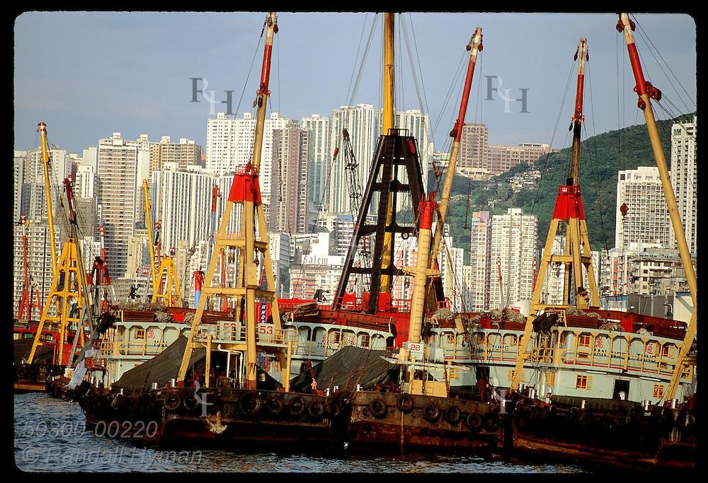 Cargo ferries sit at Wan Chai dock below hi-rise apartments of Causeway Bay; Hong Kong Island. Hong Kong