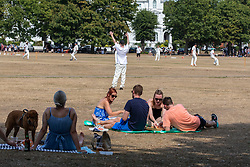 © Licensed to London News Pictures. 08/08/2020. London, UK. Members of the public enjoy a game of cricket while picnicking on Richmond Green in South West London as temperatures reach to 35c for the second day in a row. Thousands of sun seekers have flocked to parks, rivers and the south coast as temperatures soar with beaches and roads becoming jammed with holidaymakers. The heat is set to continue for the rest of the week with temperatures expected reach over 30C. Photo credit: Alex Lentati/LNP