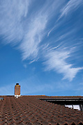 High-altitude cirrus cloud above the chimney and sloping roof of an English suburban house, on 30th May 2021, in Nailsea, North<br />  Somerset, England.