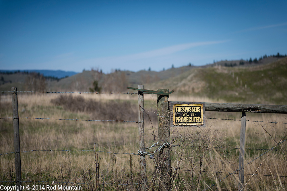 A sign proclaiming 'Trespassers will be Prosecuted' labels a fence near the topside of a hill in British Columbia's Okanagan valley.