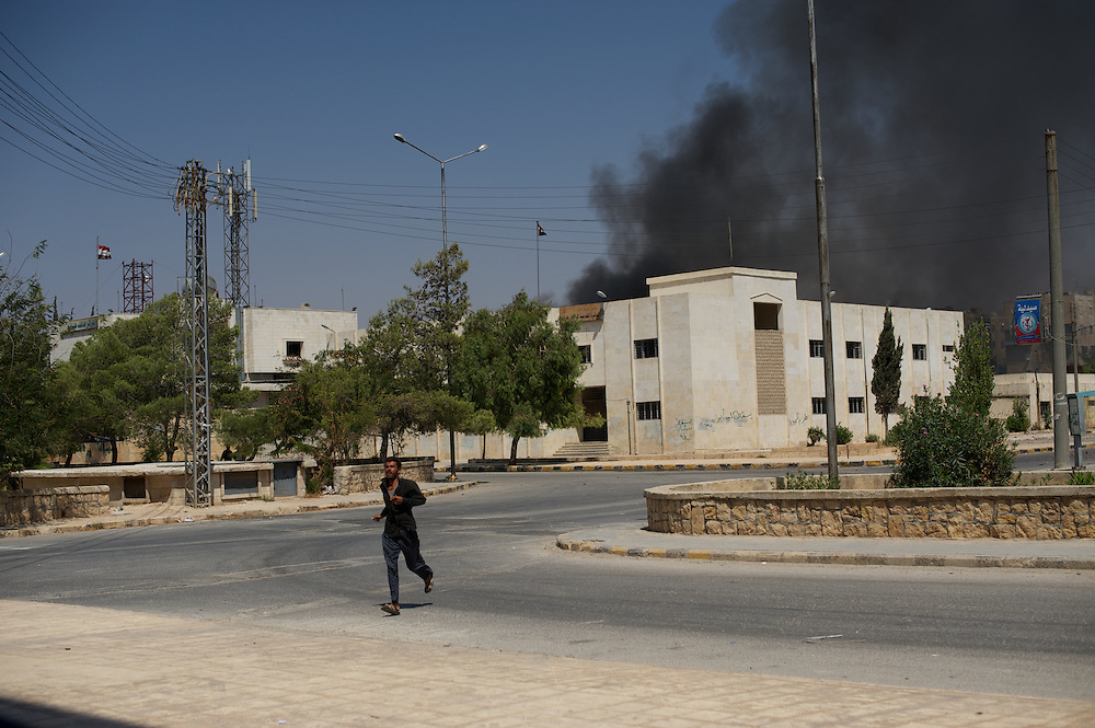 August 15, 2012 - Aleppo, Syria: A man flees the scene of an explosion cause by a Syrian army air strike on a communication center in northern Aleppo. (Paulo Nunes dos Santos/Polaris)