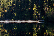 A calm fall day offers a great reflection at the floating bridge at Sasamat Lake in Port Moody, British Columbia, Canada.  White Pine Beach  is just around the corner from here and along with Sasamat Lake is within Belcarra Regional Park.
