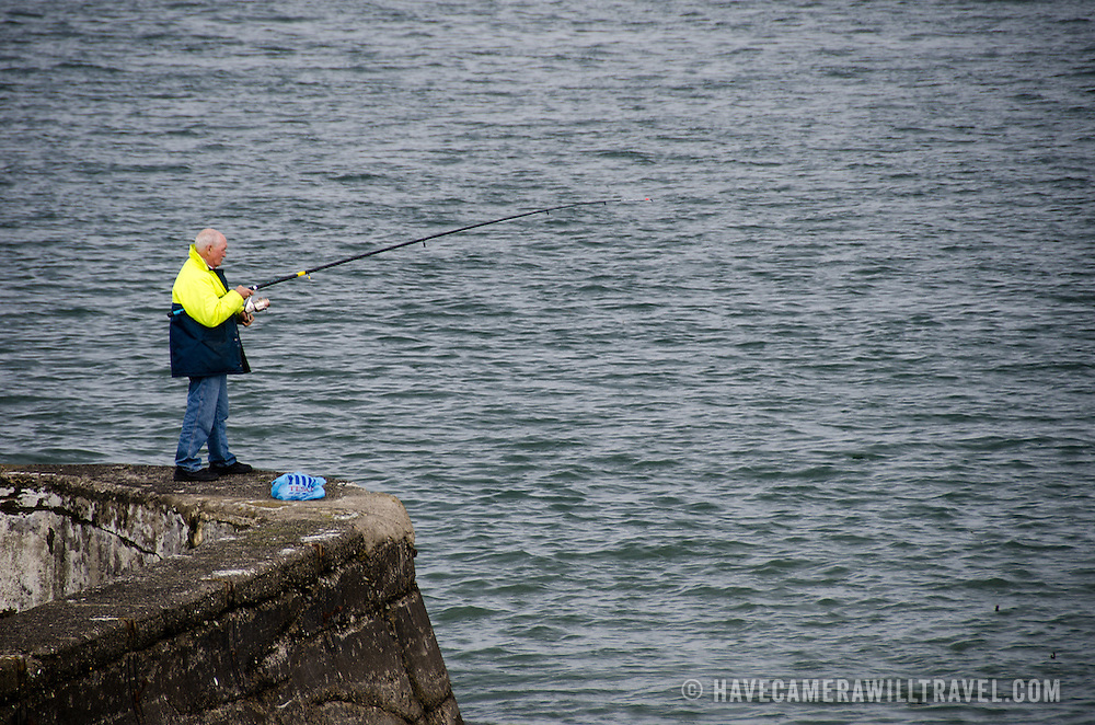 A man fishes from a stone wall in Beaumaris on the island of Anglesey of the north coast of Wales, UK.