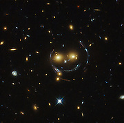 Hubble Spots a Cluster of Galaxies That Looks like a Massive Smiley Face<br /> <br /> Hot on the heels of their new and improved Pillars of Creation image, NASA just published a new photo that appears to be the largest happy face in existence. The eyes alone are two different galaxies, SDSSCGB 8842.3 and SDSSCGB 8842.4, and the smile is an optical illusion caused by something called strong gravitational lensing, a phenomenon where the gravitational pull of an object is so powerful it causes spacetime to warp, effectively distorting the light around it.<br /> ©Exclusivepix Media