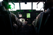 Green light from the Head-Up Display (HUD) in the cockpit of a Lockheed Martin-built C-130J Hercules airlifter. Externally similar to the classic Hercules in general appearance, the J model sports considerably updated technology. These differences include new Rolls-Royce AE 2100 D3 turboprops with Dowty R391 composite scimitar propellers, digital avionics and HUDs for each pilot). During more than 50 years of service the Hercules family has the longest continuous production run of any military aircraft in history. Strategic, automated low-level airdrops keep 60 road transport vehicles and up to 120 supple troops off hostile roads using only three flight crew.