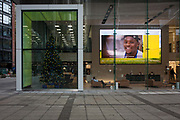 A face smiles out from a widescreen in the Aviva office foyer during a rolling video for the insurance corporate, on 9th December 2016, in the City of London, England.