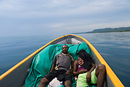Two passengers relax in the bow of a fibreglass banana boat traveling between the towns of Vanimo and Aitape on the north coast of Papua New Guinea. Given the lack of a good road on this part of the north coast, the 3-4 hour boat journey is a common means of transport between the two towns.