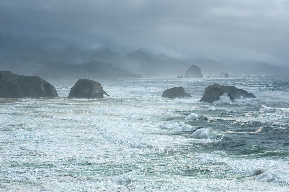 Canon Beach, Oregon Coast.  I've had dreams where I am trying to go somewhere, but each step is a great effort, as if I'm in slow motion.  Fighting the force of the wind coming off the Pacific was like that this day, as I struggled, sometimes pushed backwards, to a bluff above the chaos.  Looking straight out into the storm hurt my eyes.  I ppositioned myself as a shield against the tripod, which was vibrating like a rubber band, and tried to shoot as fast as everything unfolding before me.  The waves were urged forward with such speed that the next was upon the last as they hit the shore, and a great foam filled the shallows, while the mists trailing from the wave tops were uplifted in clouds that rose inland against the mountains that come down to the sea.  Back on my bluff, forces collide...the forces that have driven the sea to such intensity, and the more sublime forces that have driven me here, forces I am powerless to resist.  Risk drives me into danger, beauty stamps itself in my memory, adventure heightens my senses.  And love--love always drives me, with a heart that is either confident or a heart that's broken, and just doesn't care.  Sometimes I am so full of purpose that I lose perspective.  And so I am driven, eventually, into oblivion.