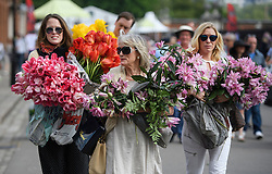 © Licensed to London News Pictures. 28/05/2016. London, UK. Members of the public carry exhibitors' plants from the 2016 Chelsea Flower show which ended today (Sat). A wide array of unusual and striking display items can be purchased on the closing day of The Royal Horticultural Society flagship flower show,  held at the Royal Hospital in Chelsea since 1913.  Photo credit: Ben Cawthra/LNP