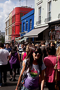 Crowds in the sun on Portobello Road market, Notting Hill, West London. This famous Sunday market is when the antique stalls come out as well as the food stalls.