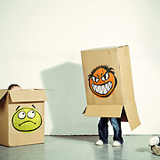 Kids playing with cardboard boxes with faces drawn on them.